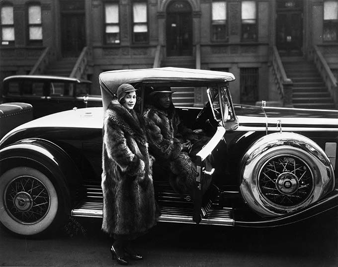 James Van Der Zee, A Harlem Couple Wearing Raccoon Coats Standing next to a Cadillac on West 127th Street, 1932